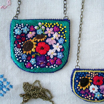 Hand embroidered colorful flowers on navy blue fabric bib necklace with leather backing and brass chain