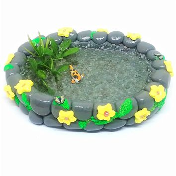 Fairy garden accessories. Miniature koi fish pond with yellow flowers.
