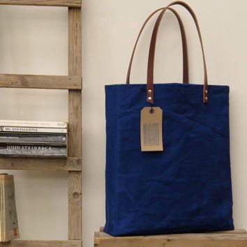 Oversized tote. Thick leather straps. Washed electric blue canvas. Blue/white cotton stripe lining.