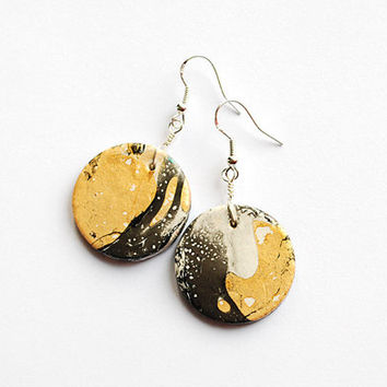 Artistic golden and black earrings. Expressive bohemian statement jewelry with random pattern.