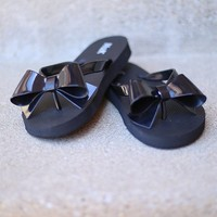 Tell Me A-bow-T It Flip Flops in Black