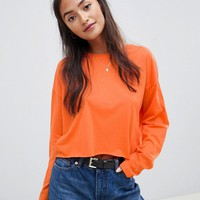 ASOS DESIGN crop boxy t-shirt with long sleeves in orange at asos.com