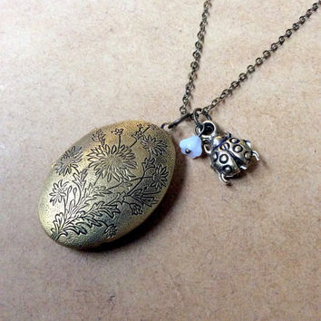 floral oval keepsake locket necklace with ladybug charm and bell flower bead