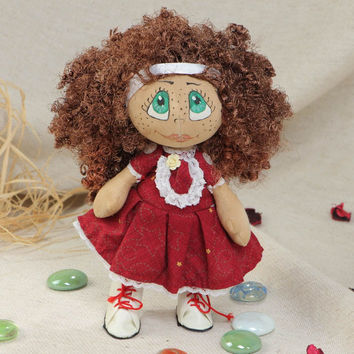 Handmade interior designer fabric soft doll girl in dark red dress with curly hair