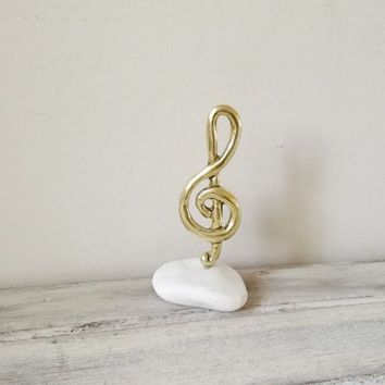Treble clef sculpture, brass treble clef on white stone, treble clef art object, brass music sculpture, metal treble clef paperweight