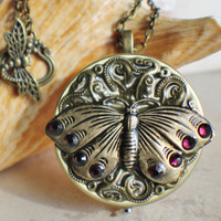 Music box locket,  round locket with music box inside, in bronze with filigree and butterfly adorning front cover.