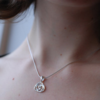 Mini sterling silver rose pendant with hammer texture handmade in a small swirl flower design by Canadian jewellery artist Melissa Pedersen