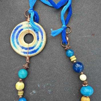 Blues and creams pendant ceramic necklace. Ceramic, wood, stone, and copper metal.