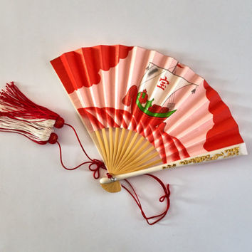 Small Japanese folding hand fan made of bamboo, plastic and paper. Red with picture of sea and ship. Decorated with red thread. Vintage fan.