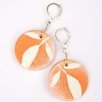 Peach earrings with leverback hooks. Painted white leaves on pink circular pendant. Handmade jewelry.