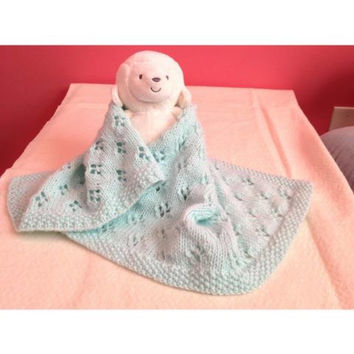 Hand knit baby blanket and hat to keep baby warm while riding around in the car