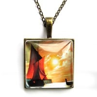 Pendant charm with glass dome.Antique brass colour. Ship at the sea. Sunset