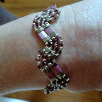Beaded bracelet in zig zag pattern with lilac tila beads,silver Miyuki seed beads,nickel 1/2 tila beads,and fire mountain gems.Handmade