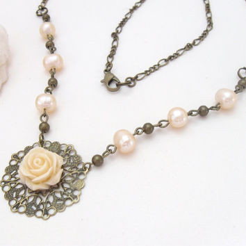 Pearl necklace with antiqued brass filigree and ivory rose