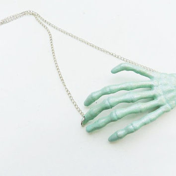 Pastel skeleton hand necklace in mint green with glitter finish