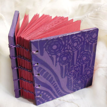 Tiny handpainted sketchbook with purple floral pattern outside and pink pastel paper inside