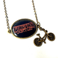 Stranger Things necklace: Friends Don't Lie resin cabochon pendant and bicycle charm