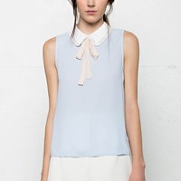 It's pretty feminine blouse top features a white chiffon Peter Pan collar (white crochet trim) neckline with removable peach color pussybow strap, sleeveless design, keyhole back with an eye hook closure. Unlined. Pair with skinny jeans, skirt, denim short