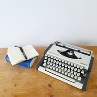 1970s White Working Vintage Manual Olympia Traveller Deluxe Portable Typewriter. In Good Cosmetic Condition. Case & Instructions Included.
