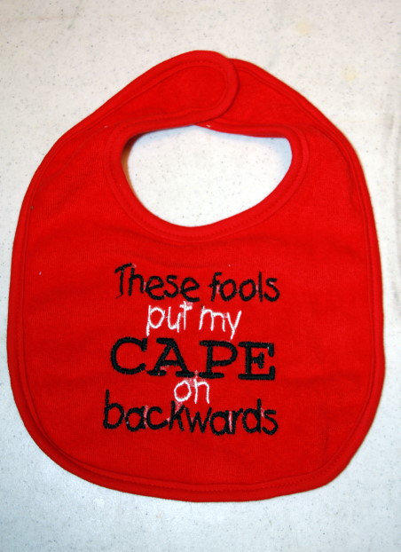 Cape bib in red with black and white writing by KenaKreations
