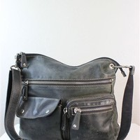 Fossil black leather cross body shoulder bag with slight distress over the exterior and zipper top closure