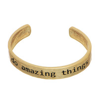 "Worn gold tone cuff bracelet stamped ""do amazing things""."