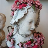 Sweet face lady bust statue wrapped in pink vintage millinery garland