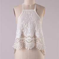 Ivory halter top with a crochet lace trim on the front.