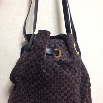 70s Vintage Gucci navy and brown suede leather mini hobo bucket shoulder purse with GG print and a golden hardware and kiss lock closure.