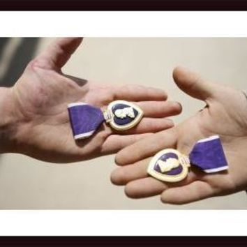 Purple Heart recipients display their medals in their hands., framed black wood, white matte