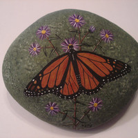 Monarch Butterfly and Asters hand painted on a rock by Ann Kelly.