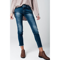 Distressed skinny jeans with frayed edges at hems