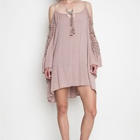 This slip on style loose fitting crinkle fabrication gauze dress features a v-neckline with self-tie rope and tassel detailing, cold shoulder three quarter bell sleeve with crotchet insert, spaghetti straps, loose fitting dress with asymmetrical bottom hem