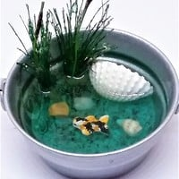 Fairy garden miniature koi pond in mini washtub with shells and cat tails.