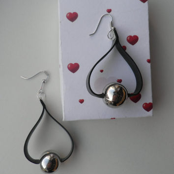 Silver earrings.The earrings consists of a strip of black rubber underneath a silver bead.The earrings are 2,36 inches long and handmade.
