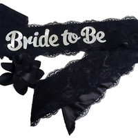"Black ""Bride To Be"" Lace & Satin Bachelorette Party Sash With Flower Pin Accessory - Also for Hen Party Bridal Shower (Black with Silver Lettering)"