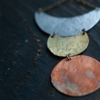 Lunar phase necklace in mixed metals, aluminium, brass and copper, hammered and fire oxidised for a rainbow patina.