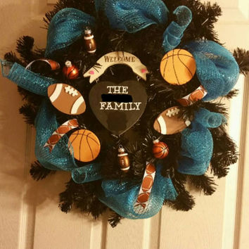 Football and basketball custom made to order 27 inch door hanging wreath, blue and black colors, wooden family name sign in the middle. Fan