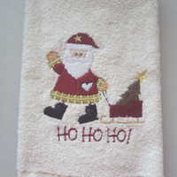 Christmas Beige Tea Towel with embroidered Santa pulling a sleigh and the words HO HO HO