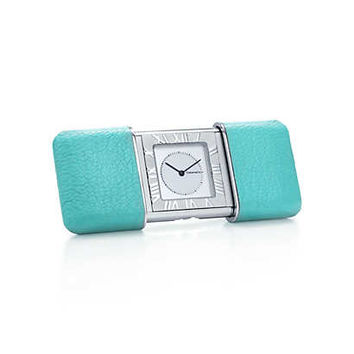Tiffany & Co. - Atlas® travel alarm clock in rhodium with leather slide cover.