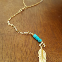 Gold plated single layer necklace, gold feather charm and turquoise beads.
