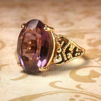 Large amethyst color purple 18 K GE gold ring with ornate side detailing. Size 8.75.