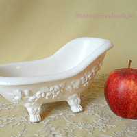 Old dollhouse bathtub, made of white porcelain china with molded rose décor standing on animal feet, vintage dollhouse or doll furniture