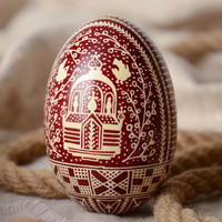 Red and white handmade painted goose egg decorated using waxing technique