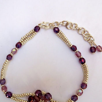Beaded bracelet in purple and lilac fire mountain gems and silver Miyuki seed beads with a flower pattern in the center. Handmade