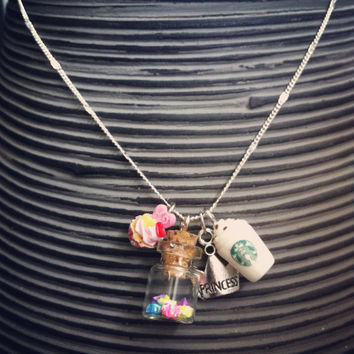 Cute charm necklace with Starbucks cup, A mini cupcake, a glass bottle (hand folded mini stars) and a tiara :)