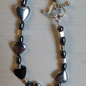 Hand beaded hematite heart bracelet with metallic square beads and heart toggle clasp