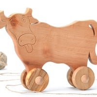 Funny wooden cow toy on wheels