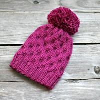 Knit honeycomb hat for women in fuchsia pink with pompom