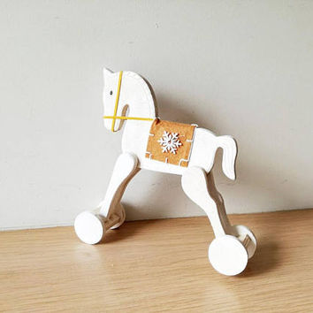 Christmas horse on wheels, white rocking horse retro toy, white horse with brown blanket saddle and a snowflake, decorative Xmas horse